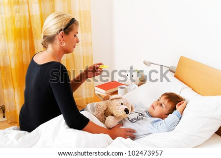 a mother and sick child in bed. flu. childhood diseases. - stock photo