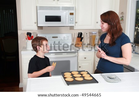 a mother and son enjoy hot fresh baked cookies after school in the kitchen - stock photo