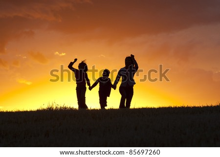 A mother, daughter, and son skip along at sunset. - stock photo