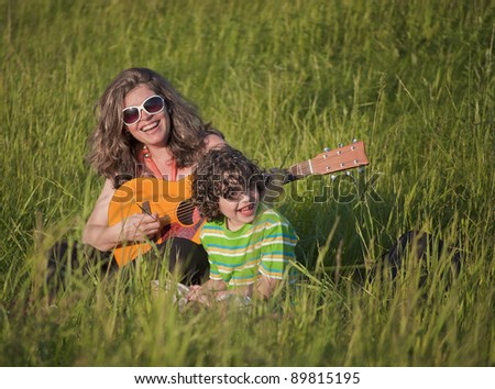 A mother enjoys a sunny day with his little son - stock photo