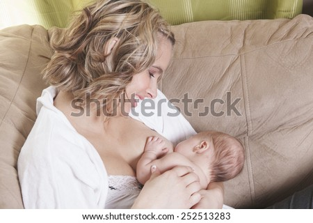 A mother feeding his baby on the sofa - stock photo