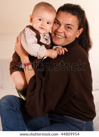 A mother  holding her baby in her arms - stock photo