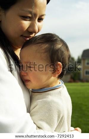 A mother holding her crying cute baby boy - stock photo