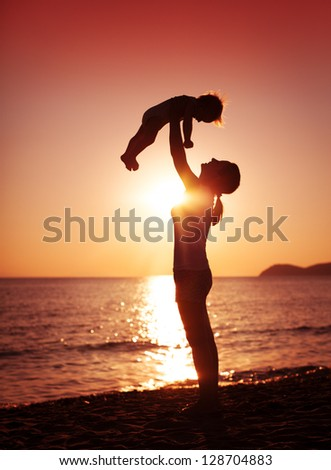 A mother holding her young child up high. - stock photo