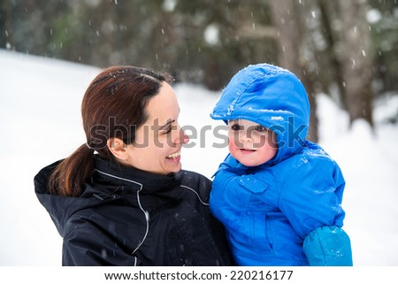 A mother holds her happy baby son smiling at him outside while its snowing during the winter season.  He has a look of wonder on his face.  - stock photo