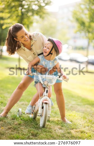 A mother hugs her daughter from behind, as daughter wearing a pink helmet looks up towards her mother, laughing and proud. She has just learned to ride her bike by herself, and is proud of herself. - stock photo