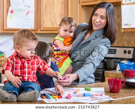 A mother in the kitchen plays with her babies - stock photo