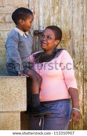 A mother is talking to her son before his first day of school. - stock photo
