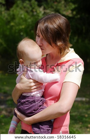 A mother kissing her cute baby daughter - stock photo