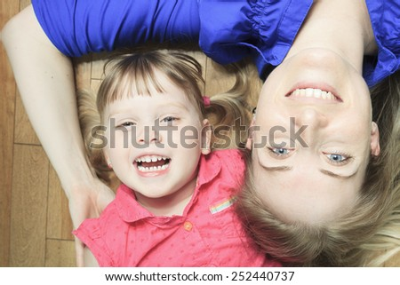 A mother lay in the living room floor with daughter - stock photo
