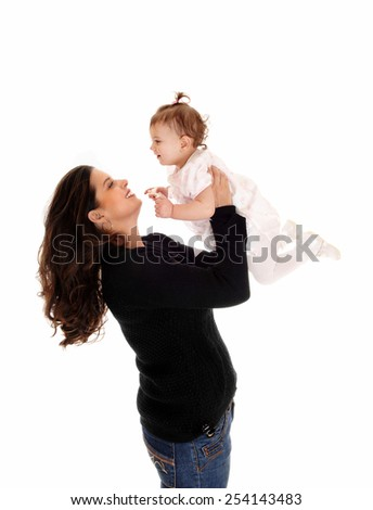A mother lifting up her daughter baby, standing isolated for white