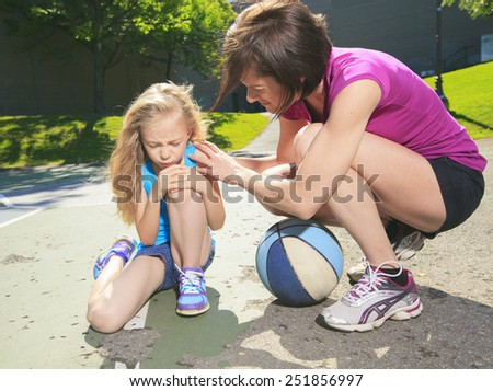 A mother play basketball with his daughter how have injury - stock photo