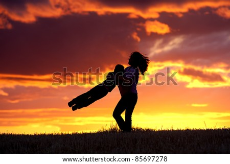 A mother plays with her son by swinging him in the air. - stock photo