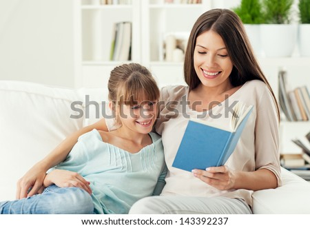 A mother reading a story to her daughter. - stock photo