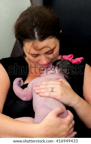 A mother snuggles her newborn baby right after giving birth at home. - stock photo