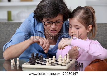 A mother teaching her daughter how to play chess. - stock photo