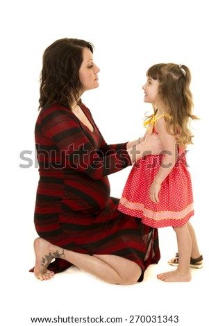 A mother trying to talk to her daughter with a serious expression, while the little girl is laughing. - stock photo