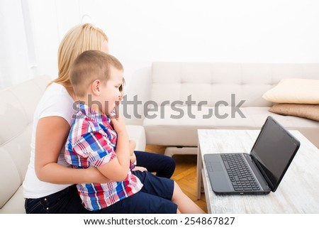 A mother using with her son and daughter a laptop computer.  - stock photo