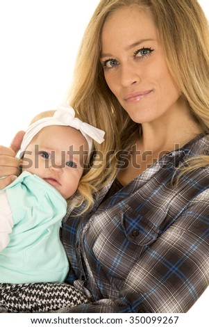 a mother with a small smile and her baby girl in her arms. - stock photo