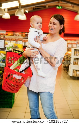 A mother with baby daughter in a grocery store - stock photo