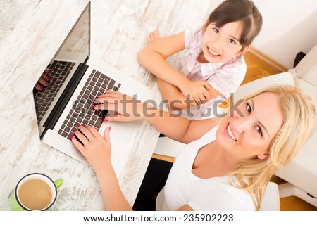 A mother with her daughter looking at a Laptop at home.  - stock photo