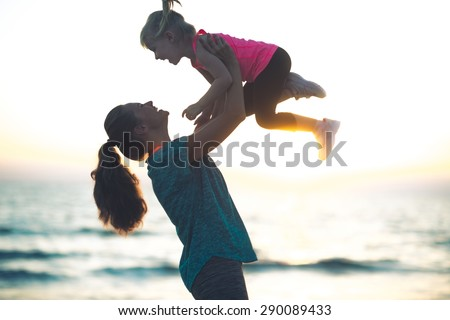 A mother with her hair pulled back in a ponytail is lovingly throwing her child up in the air at sundown. You can practically hear the joyful giggles... - stock photo