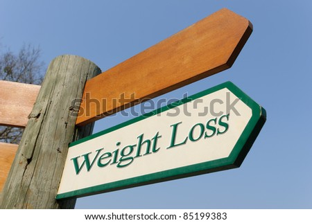 A motivational green and white wooden signpost pointing towards weight loss on sunny blue sky - stock photo