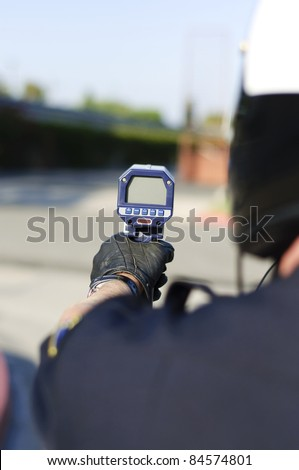 a motorcycle police officer aiming his radar gun a traffic. - stock photo
