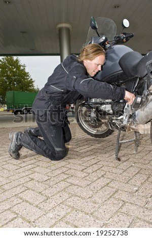 A motorcyclist inspecting his motorbike at a gas station, looking worried - stock photo