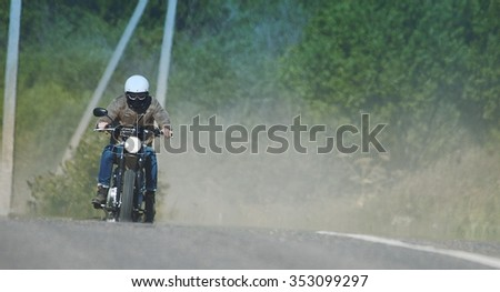 A motorcyclist rides on retro motorcycle on the road. - stock photo