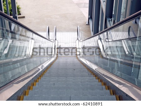 A motorized conveyor escalator leading downward and out. - stock photo