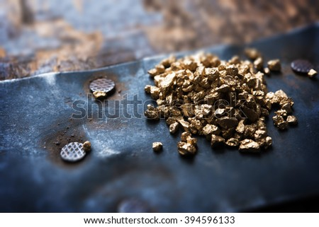 a mound of gold on a old wooden chest. Shallow depth of field.  - stock photo