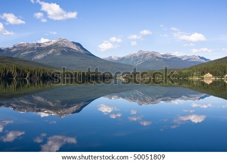 A mountain landscape is perfectly reflected in the water of Lake Yellowhead,  Canada. - stock photo