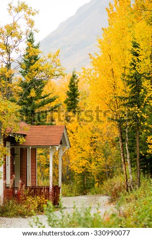 A mountain trail leads past a beautiful cabin entrance - stock photo