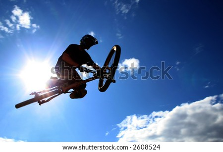 A mountainbiker flys across the sky during a freeriding contest held in Whistler, BC. - stock photo