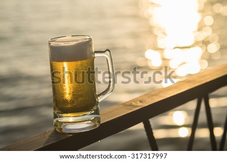 A Mug of Cold Beer with the Bokeh of the sea background in the evening time - stock photo