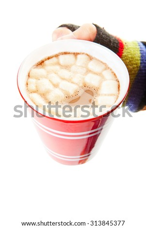 A mug of hot chocolate, complete with miniature marshmallows, held by a mittened hand. Shot on white background. - stock photo
