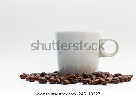 A mug standing in coffee beans isolated on white background - stock photo