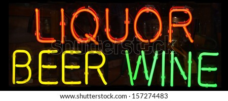 A multi colored neon sign reading Liquor Beer Wine - stock photo