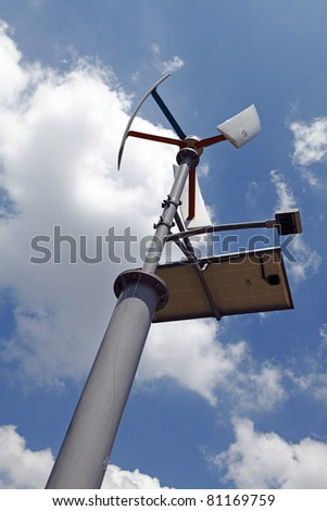 A multi energy generating street light device using sustainable solar power and wind energy via a wind turbine, against a blue cloudy sky. - stock photo