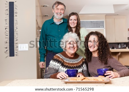 A multi generation portrait of happy grandparents with their daughter and granddaughter spending time together - stock photo