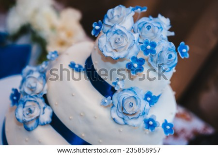 a multi level white wedding cake on a white base and blue flowers on top. Wedding cake in white and blue combination, adorned with flowers and ribbons  - stock photo