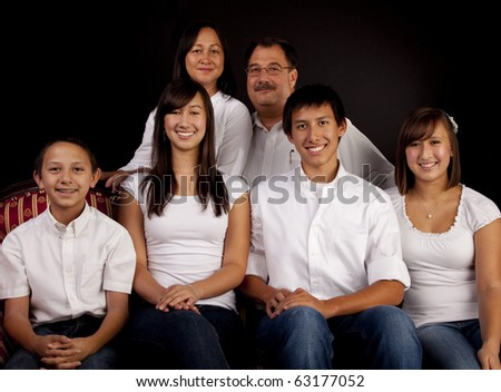 A multicultural family of six in a seated formal  studio portrait with a black  background. - stock photo