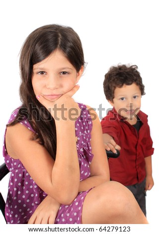 A multiracial girl with hand on her chin looking pensive and a toddler  boy in the background - stock photo