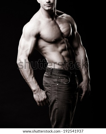 a muscular man posing artistic, on black background - stock photo