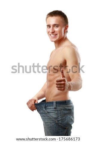 A muscular man showing how much weight he lost - stock photo