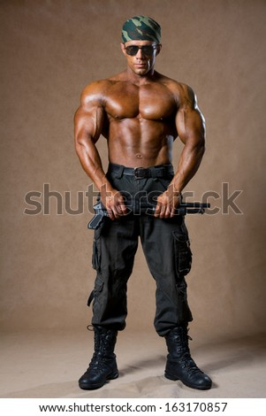 A muscular man with a gun in full view. The guy in the soldiers' boots - stock photo