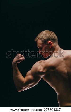 a muscular young man showing his biceps isolated on black background - stock photo