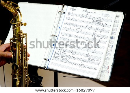 A music score and a musician whit saxophone - stock photo