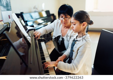 a music teacher with the pupil at the lesson piano - stock photo